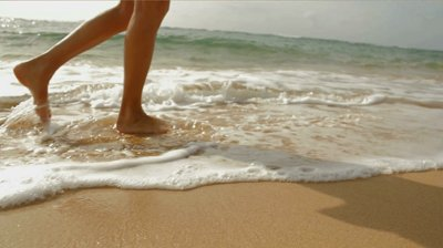 stock-footage-a-woman-walks-on-the-beach-leaving-footprints-in-the-sand